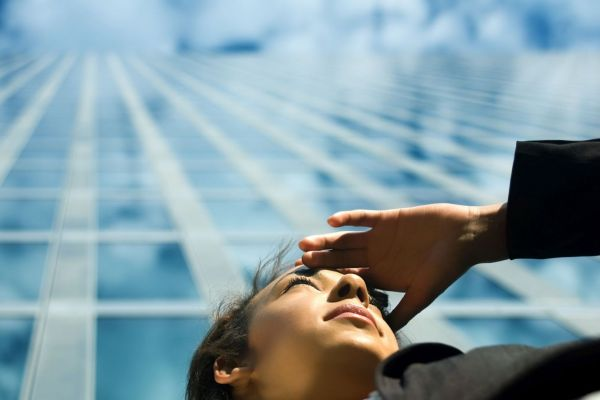 Frau vor einem Gebäude, die in die Ferne schaut