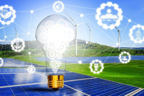 Glühbirne mit Zahnrädern vor Windrädern und einer Solaranlage und umrundet von Symbolkugeln für verschiedene Energietechnologien (Symbolbild)
