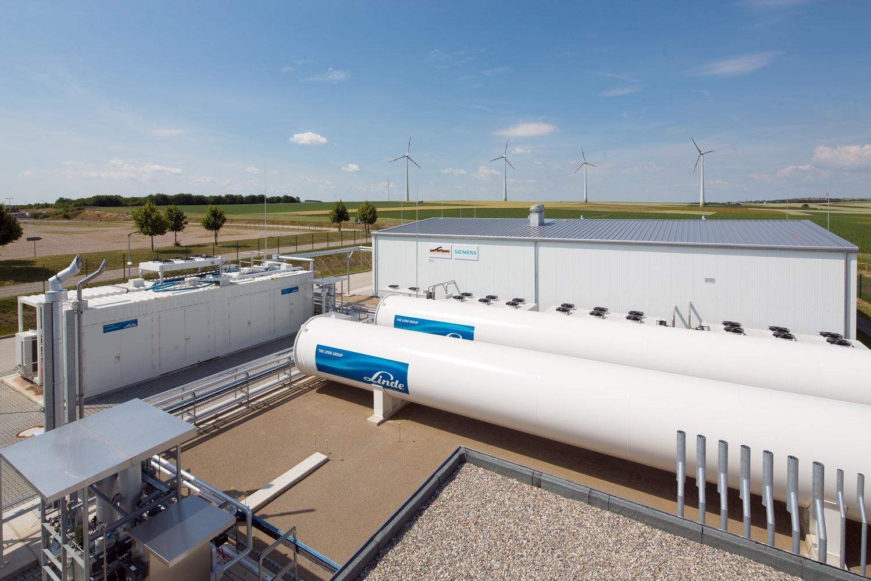 Anlage zur Umwandlung von Wasser in Wasserstoff und Sauerstoff. Vier Windräder im Hintergrund.