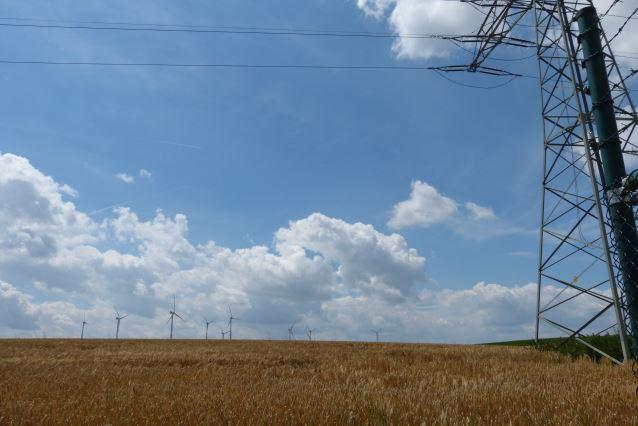 Ein Strommast steht an einem Feldrand. Am Horizont drehen sich Windräder.