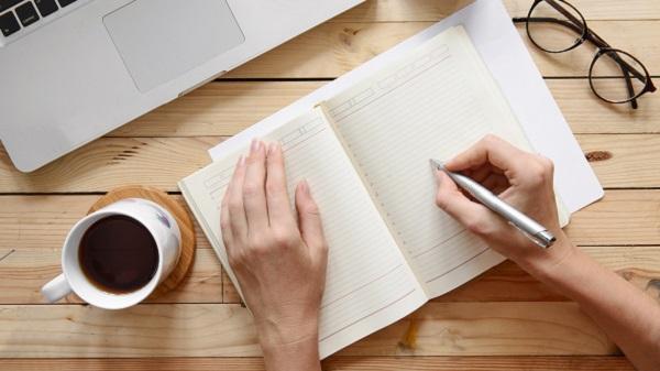 Hand schreibt in einem Notiz Buch dahinter steht ein Laptop