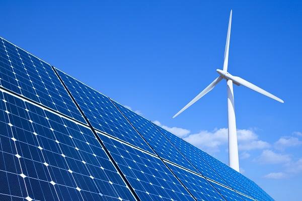 Solarpanel im Vordergrund und Windrad im Hintergrund