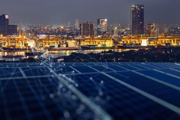 Solarmodule mit Stadt bei Nacht im Hintergrund